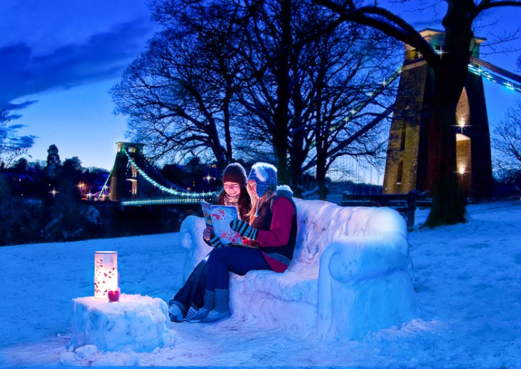 Bristol Editorial Photography - Girls sitting on snow sofa in front of Clifton Suspension Bridge at twilight