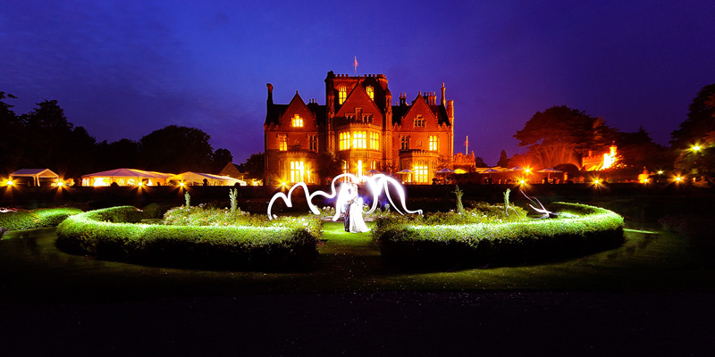 bride and groom in front of tortworth court at night